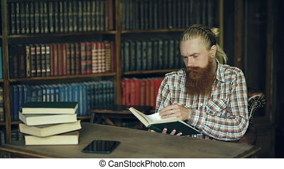 Young bearded student in library reading a book and prepare for exams