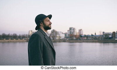 Young bearded tourist man in hat and coat watching cityscape...