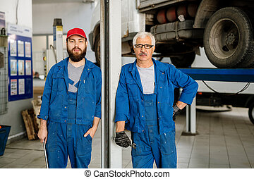 Young bearded worker and technical master in workwear looking at you