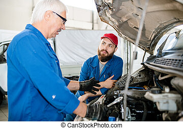 Young bearded worker of technical service looking at his mature colleague