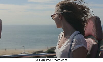 Young beatiful woman traveling thruought coastline with beach and ocean by tourist sightseeing bus, in sunglasses
