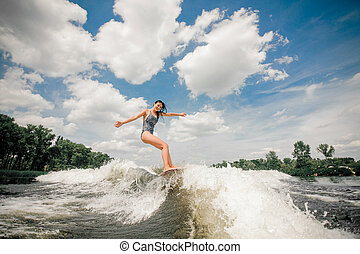 Young beatutiful woman riding on the wakeboard