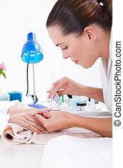 beautician applying manicure - young beautician applying ...