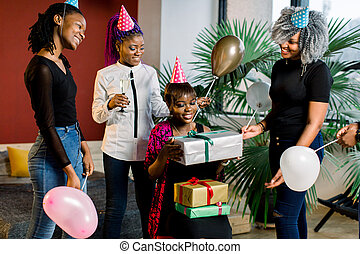 Young beautiful African American girls with balloons and hats celebrate birthday and give birthday gifts.