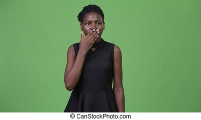Young beautiful African businesswoman covering mouth looking...