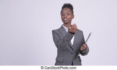 Young beautiful African businesswoman directing with...