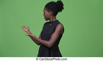 Young beautiful African businesswoman presenting something