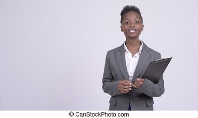 Young beautiful African businesswoman presenting something with clipboard
