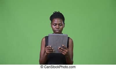 Young beautiful African businesswoman using digital tablet