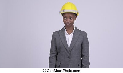 Young beautiful African businesswoman with hardhat thinking...