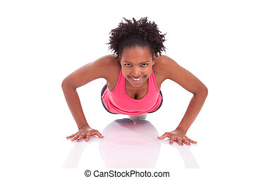 Young beautiful african fitness woman doing push up exercises on floor, isolated on white background