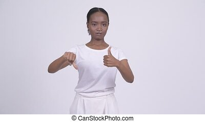 Young beautiful African woman choosing between thumbs up and...