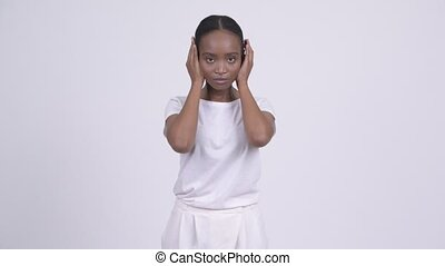 Young beautiful African woman covering ears as three wise...