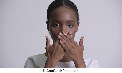 Young beautiful African woman covering mouth as three wise...
