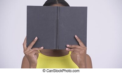 Young beautiful African woman hiding behind book - Young...