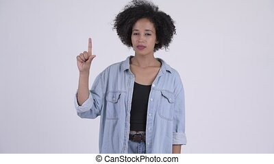 Young beautiful African woman pointing up