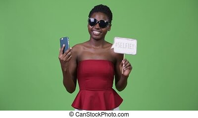 Young beautiful African woman taking selfie - Studio shot of...