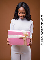 Young beautiful African Zulu businesswoman against brown backgro