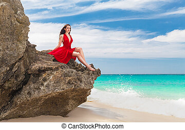 young beautiful alone woman in red dress sitting on the rock...