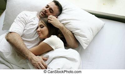Young beautiful and loving couple kiss and hug into bed while waking up in the morning. Top view of attractive man kissing and talking his smiling wife