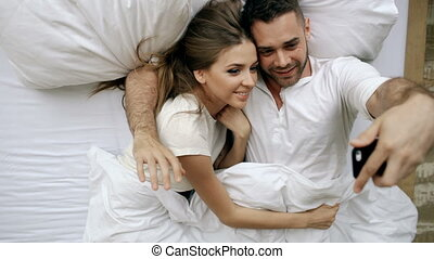 Young beautiful and loving couple take selfie picture on smartphone camera and kiss while lying in bed at the morning