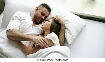 Young beautiful and loving couple talk and hug into bed while waking up in the morning. Top view of attractive man chatting his smiling wife