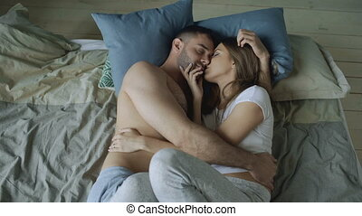 Young beautiful and loving couple kissing on bed in the morning