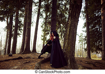 Young beautiful and mysterious woman in woods, in black cloak with hood, image of forest elf or witch