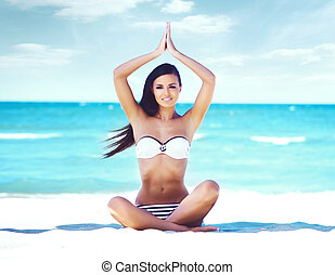 Young, beautiful and sexy girl meditating on a summer beach....