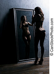 Young, beautiful and sexy woman posing and looking in the mirror