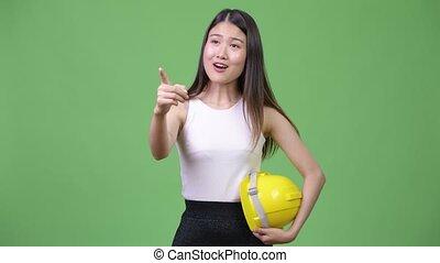 Young beautiful Asian businesswoman as engineer directing -...