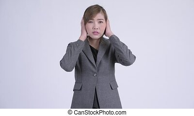 Young beautiful Asian businesswoman covering ears as three...