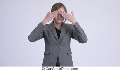 Young beautiful Asian businesswoman covering eyes as three...