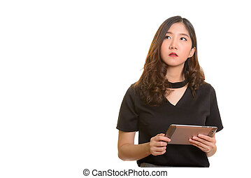 Young beautiful Asian businesswoman holding digital tablet while