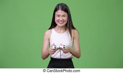 Young beautiful Asian businesswoman playing games
