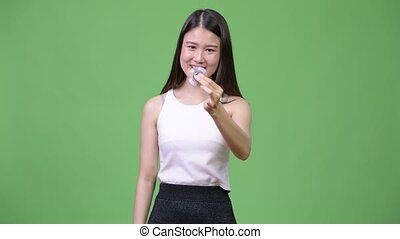 Young beautiful Asian businesswoman playing with fidget spinner