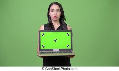 Young beautiful Asian businesswoman showing laptop