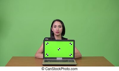 Studio shot of young beautiful Asian businesswoman against chroma key with green background