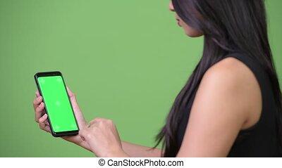 Young beautiful Asian businesswoman showing phone