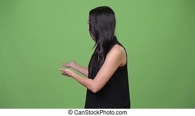 Young beautiful Asian businesswoman showing something