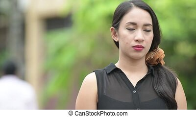 Young beautiful Asian businesswoman thinking in the streets outdoors