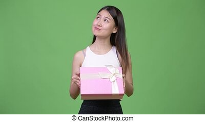 Young beautiful Asian businesswoman thinking while holding gift box