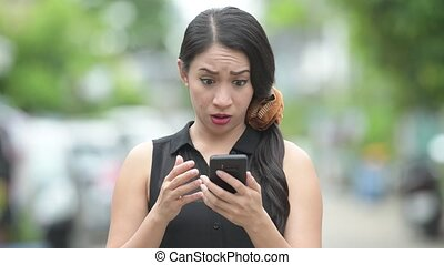 Young beautiful Asian businesswoman using phone in the streets outdoors