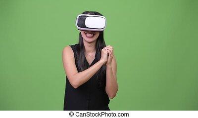 Young beautiful Asian businesswoman using virtual reality headset