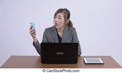 Young beautiful Asian businesswoman video calling at work -...