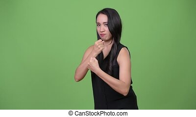 Young beautiful Asian businesswoman with fists raised -...