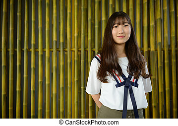 Young beautiful Asian teenage girl against bamboo fence