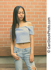 Young beautiful Asian teenage girl against brick wall