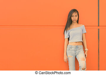Young beautiful Asian teenage girl against orange wall