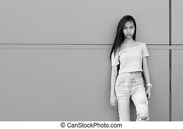 Young beautiful Asian teenage girl leaning against concrete wall outdoors